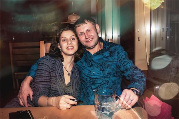 テーブルで飲み物とナイトクラブやバーで笑顔のカップル。夜の街のライフスタイルのコンセプトのナイトライフ。コピースペース