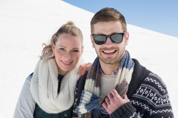 Улыбаясь пара в теплую одежду на заснеженном ландшафте