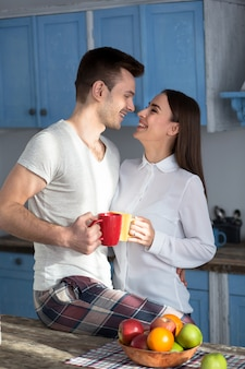 Smiling couple at kitchen looking eyes to eyes.