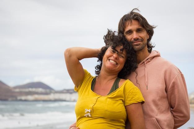 カメラを見ている笑顔のカップル。ビーチを楽しむロマンチックな愛好家はカジュアルな服を歩きます。