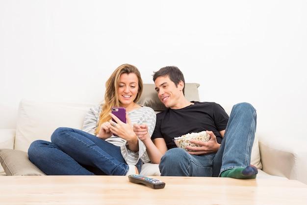 소파에 앉아 휴대 전화를보고 웃는 커플