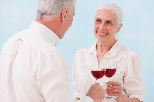 Smiling couple looking at each other while clinking wine glass