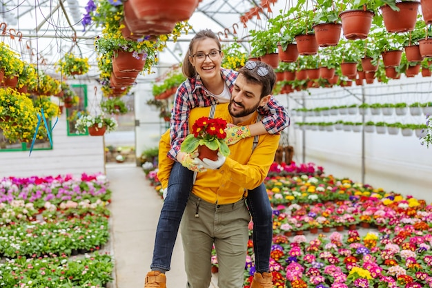 Smiling couple in love having piggyback ride in greenhouse. all around them are colorful flowers. small business owners.