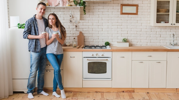 Smiling couple in love standing in kitchen