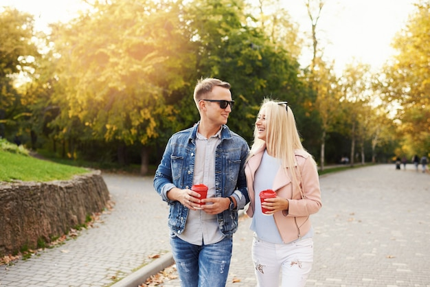 Smiling couple in love walking in autumn park, holding hands. listen to music on headphones and drink coffee to go.