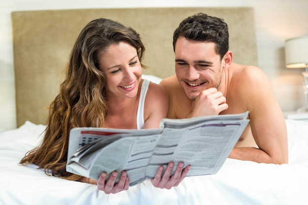 Smiling couple lying in bed with a newspaper