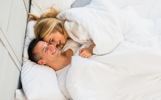 Smiling couple lying under blanket on bed