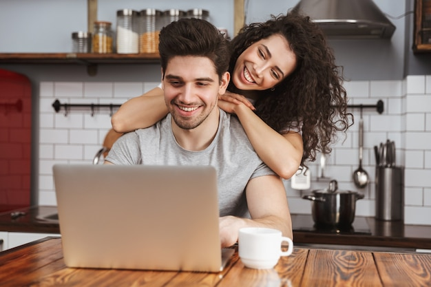 Smiling couple man and woman looking at laptop on table while having breakfast in kitchen at home