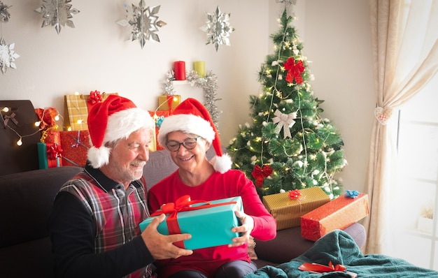A smiling couple of man and woman in santa's hats with many presents for them and for family. christmas tree on the background