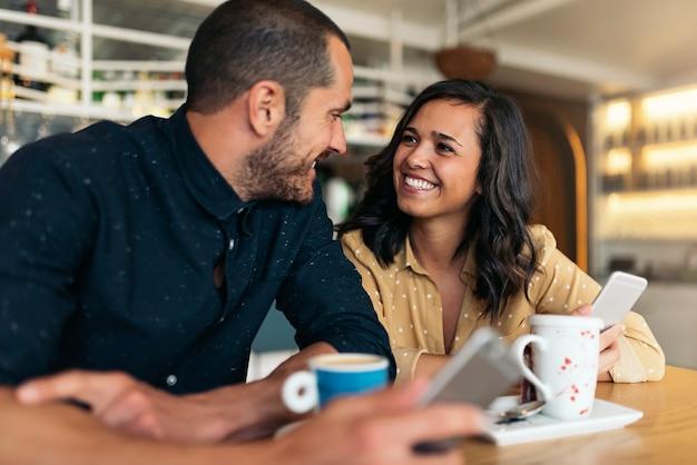 コーヒーショップで楽しんでいる恋人の笑顔のカップル。