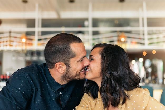 コーヒーショップでキスする恋人の笑顔のカップル。