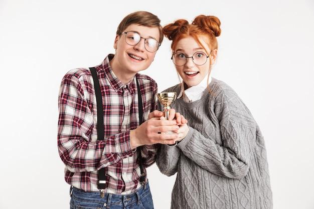 優勝トロフィーを保持している学校のオタクのカップルの笑顔