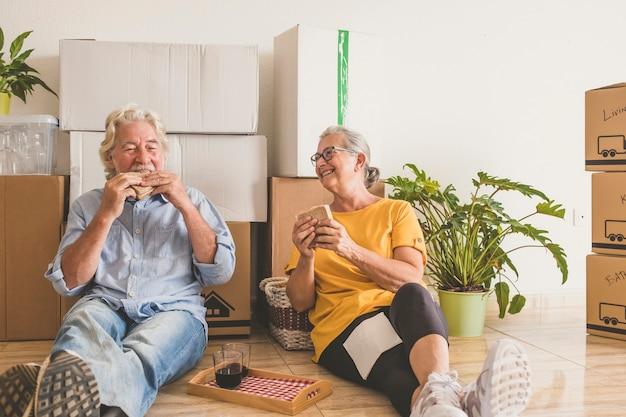 Улыбающаяся пара пожилых людей с белыми волосами, работающих в новой пустой квартире с движущимися ящиками, сидя на полу во время перерыва - концепция активных пожилых людей и новое начало, как пенсионер
