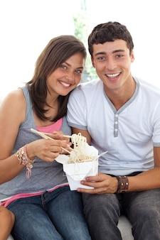 Улыбаясь пара подростков едят макароны