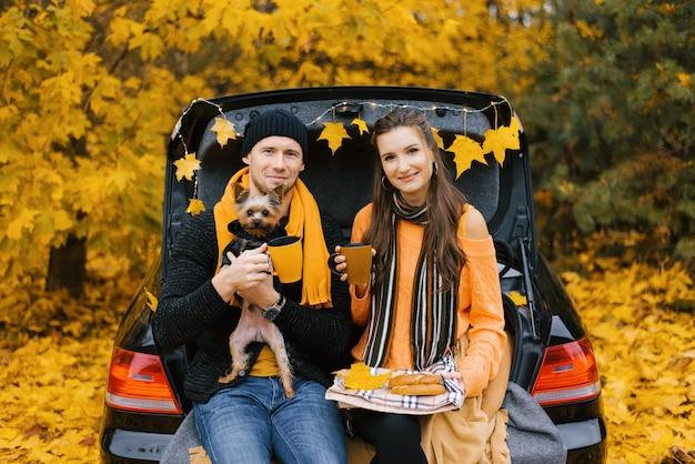 Улыбающаяся пара путешественников пьет кофе или чай, сидя на багажнике автомобиля