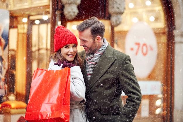 쇼핑몰 밖에 서 웃는 커플