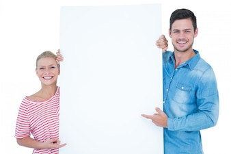 Smiling couple pointing at blank sign in their hands