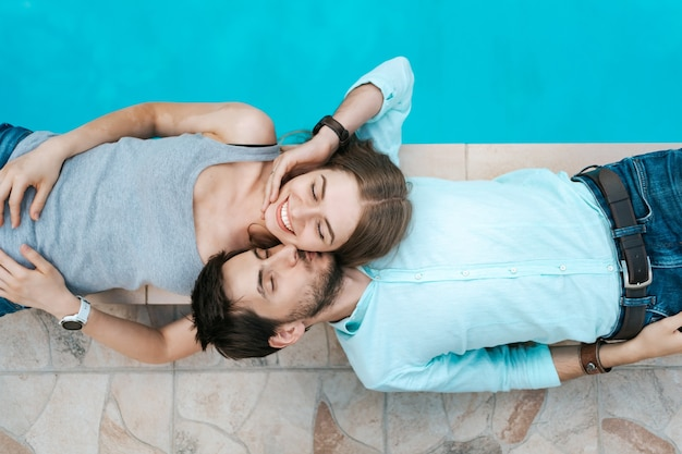 プールの近くに服を着て横たわっている笑顔のカップルの肖像画。彼らはお互いを崇拝する