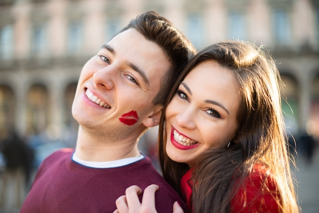 Smiling couple portrait, the man has a lipstick kiss mark on his cheek