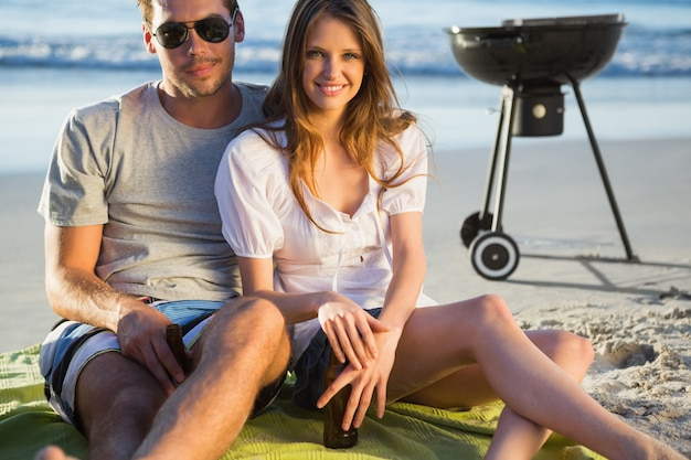 Smiling couple posing while having barbecue