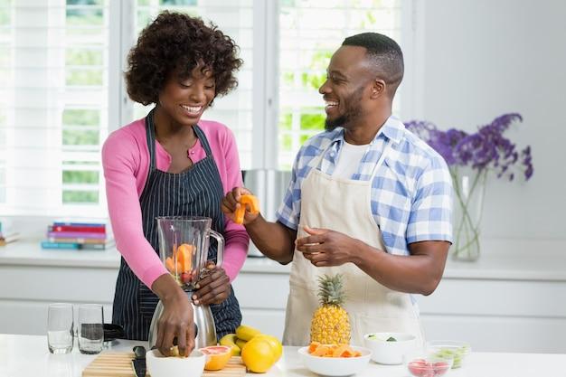 Улыбаясь пара готовит фруктовый сок в кухне