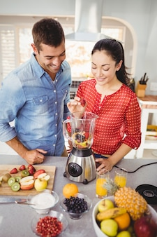 Smiling couple preparing fruit juice while standing at table
