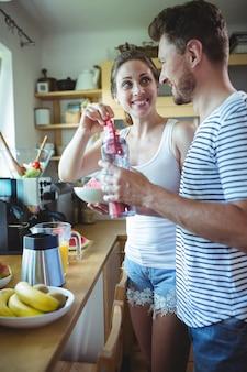 Smiling couple preparing watermelon smoothie in kitchen