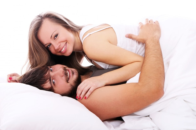 Smiling couple relax in bed