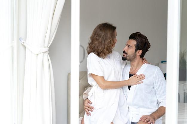 Улыбающаяся пара расслабляется и обнимаются в постели