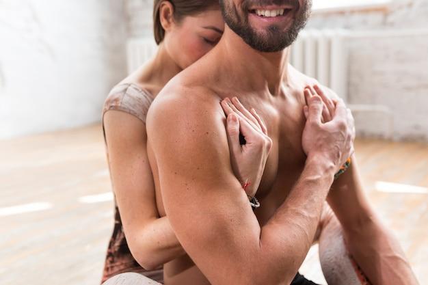 Улыбающаяся пара, расслабляющаяся и обнимающая после выполнения упражнений йоги