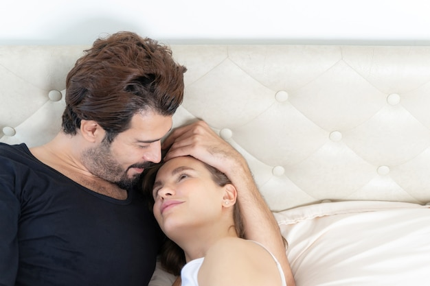 Smiling couple relaxing and couples cuddling in bed