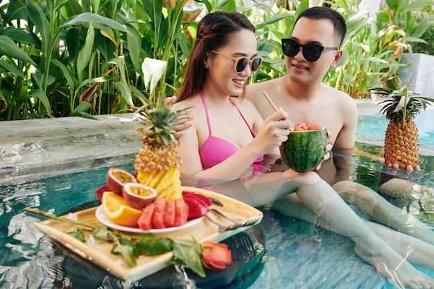 小さなプールで休んで笑顔のカップル