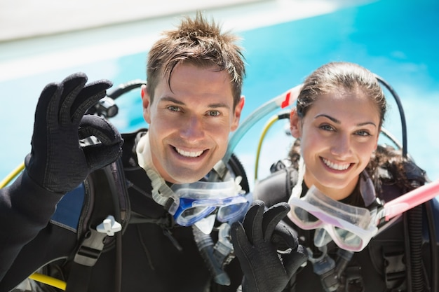 Smiling couple on scuba training in swimming pool showing ok gesture