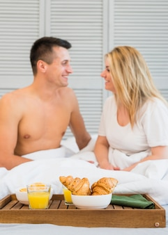 Smiling couple sitting on bed near food on breakfast table
