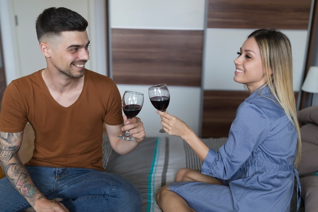 Smiling couple sitting on bed toasting wineglasses