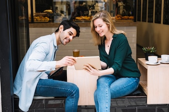 Smiling couple sitting in cafe with tablet
