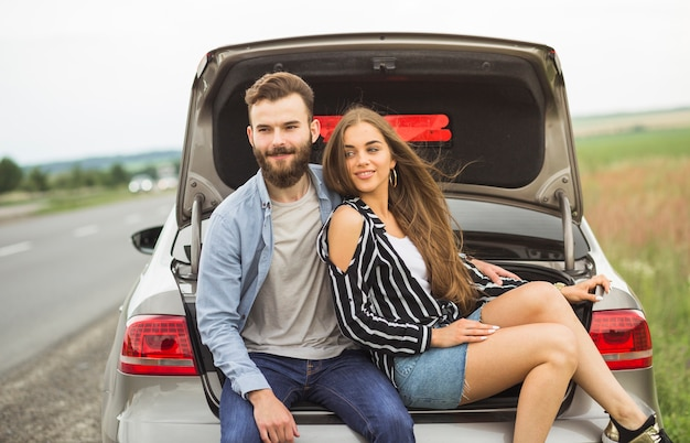 Smiling couple sitting inside the car open trunk