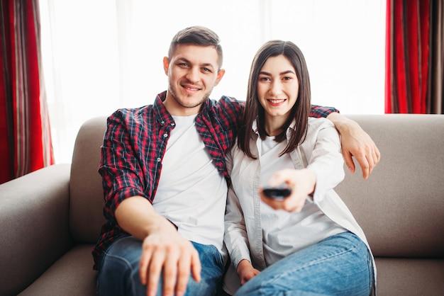 Улыбающаяся пара сидит на диване и смотрит телевизор дома, женщина с пультом дистанционного управления в руке