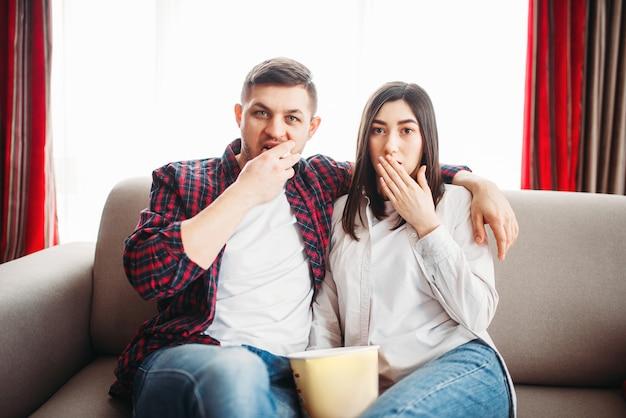 Улыбающаяся пара сидит на диване и смотрит телевизор