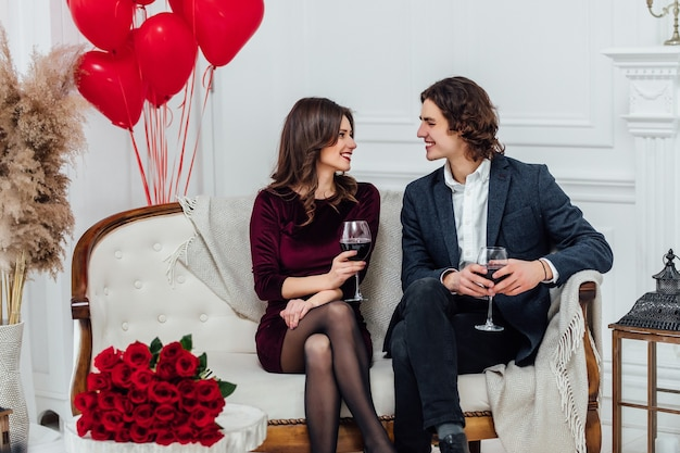 Smiling couple sitting on the sofa drinking wine and looking at each other