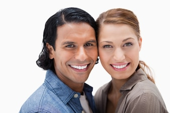 Smiling couple standing close together against a white background