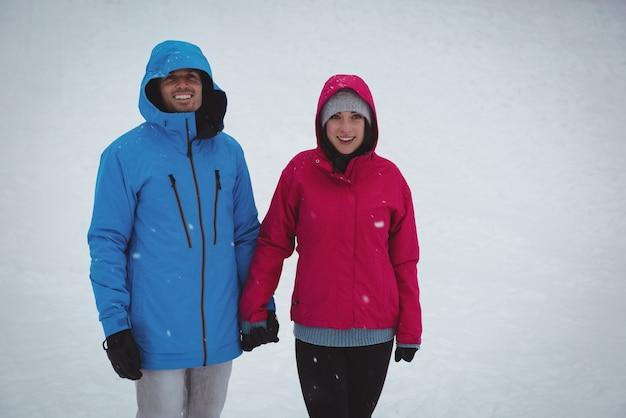 雪の森に立っている笑顔のカップル