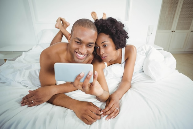 Smiling couple taking selfie on the bed at home