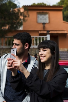 Smiling couple taking selfie with camera phone