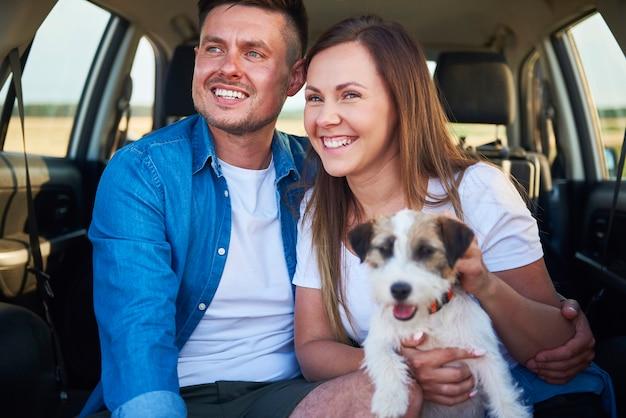 Coppia sorridente e il loro cane seduti nel bagagliaio dell'auto