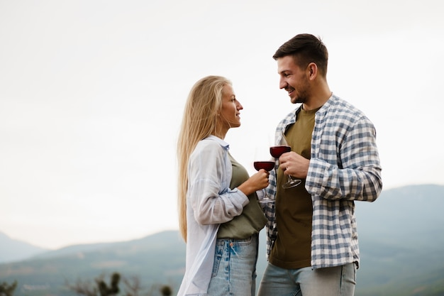 Smiling couple toasting wine glasses outdoors in mountains