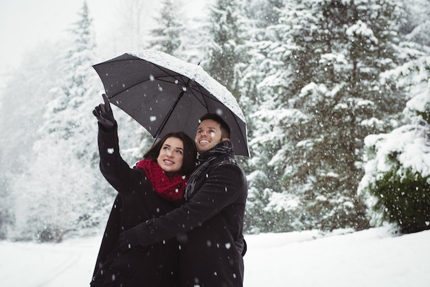 Smiling couple under umbrella pointing at view in forest during snowfall