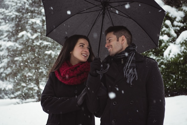 Smiling couple under umbrella standing in forest during snowfall