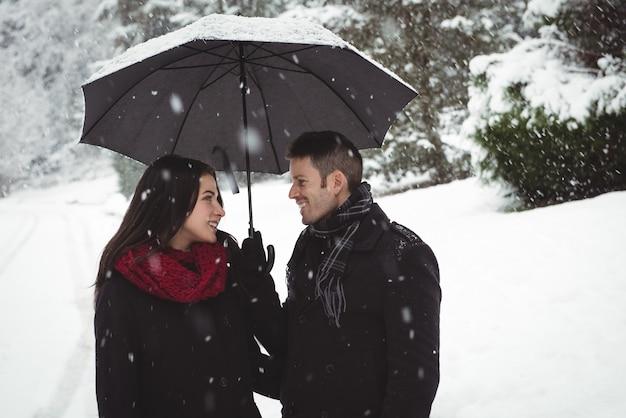 降雪時に森に立っている傘の下で笑顔のカップル