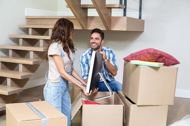Smiling couple unpacking computer from cardboard box